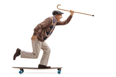 Tiro de perfil de longitud completa de un alegre senior sosteniendo un bastón y montando un longboard aislado sobre fondo blanco. Foto de archivo