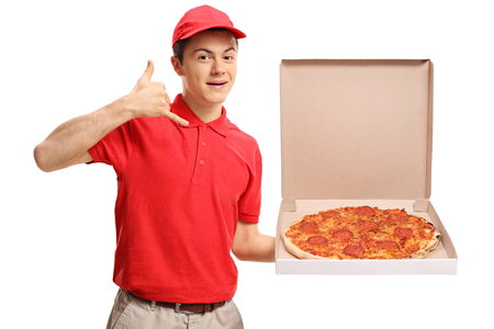 Teenage pizza delivery boy holding a pizza box and making a call me gesture isolated on white background