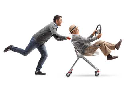 Young man pushing a shopping cart with a mature man holding a steering wheel riding inside isolated on white background