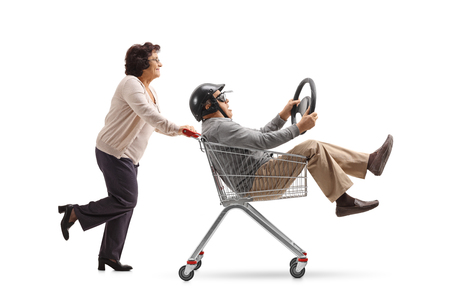Mature man with a helmet and a steering wheel riding inside a shopping cart being pushed by an elderly woman isolated on white background
