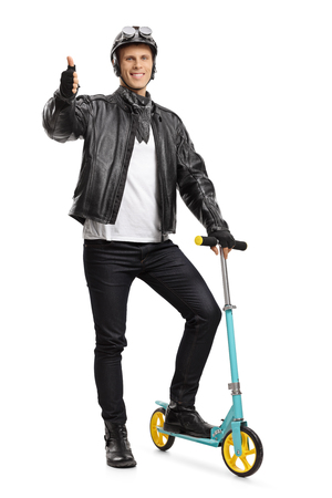 Full length portrait of a biker with a scooter making a thumb up sign isolated on white background Stock Photo