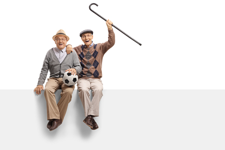 Cheerful seniors with a football seated on a panel isolated on white background