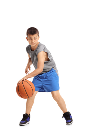 Full length portrait of a boy dribbling with a basketball isolated on white background
