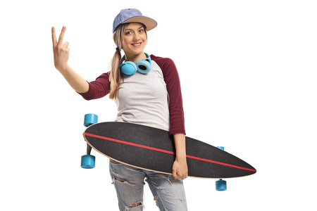 Female skater holding a longboard and making a peace sign isolated on white background