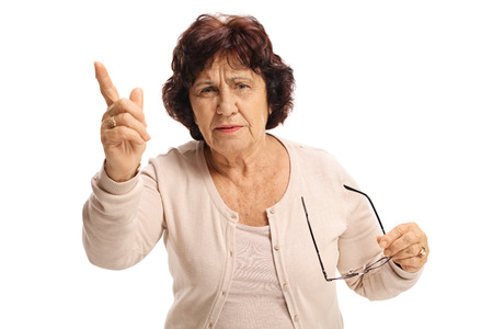 Angry elderly woman scolding someone and gesturing with her finger isolated on white background