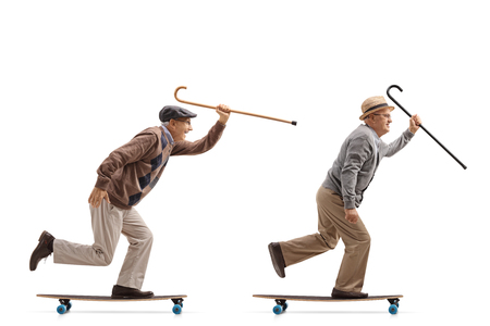 Full length profile shot of two elderly men with canes riding longboards isolated on white background Stock Photo