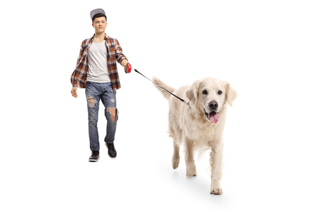 Full length portrait of a teen hipster walking a dog isolated on white background