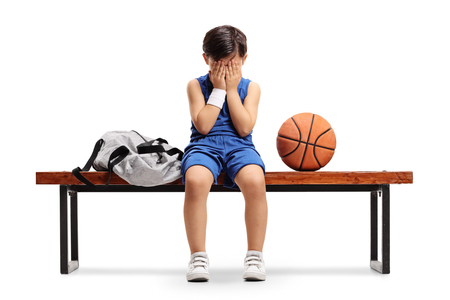 Sad little basketball player sitting on a bench isolated on white background Stock Photo