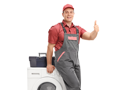Repairman leaning on a washing machine and making a thumb up sign isolated on white background Stock Photo