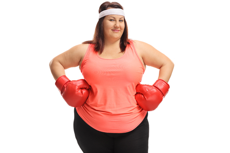 Overweight woman posing with a pair of red boxing gloves isolated on white background