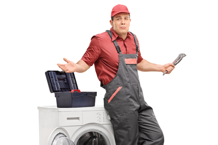 Uncertain repairman with a wrench leaning against a washing machine and gesturing with his hands isolated on white background