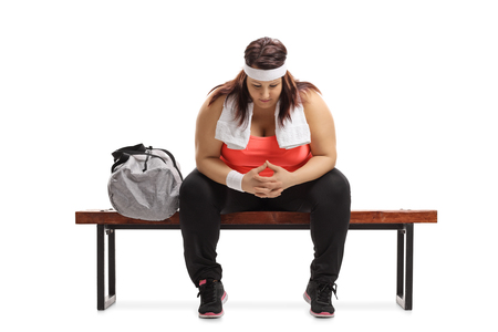 Sad overweight woman sitting on a wooden bench next to a sports bag isolated on white background