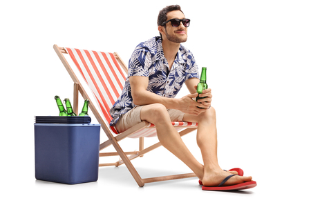 Tourist with a beer bottle sitting in a deck chair next to a cooling box and looking away isolated on white background Banque d'images