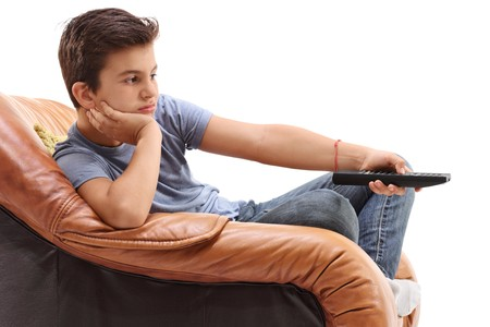 Bored boy seated in an armchair watching television isolated on white background