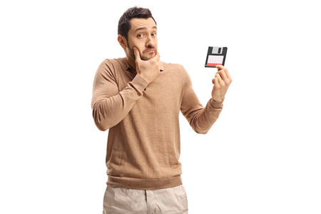 Confused young man holding a floppy disk isolated on white background