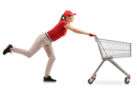 Full length profile shot of a delivery girl pushing an empty shopping cart isolated on white background