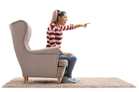 Angry young woman sitting in an armchair and arguing with someone isolated on white background