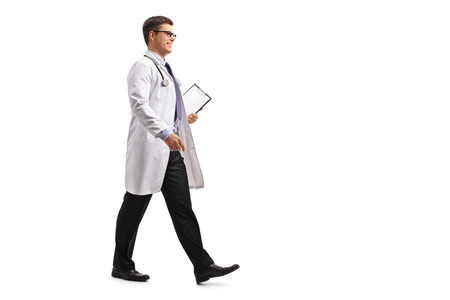 Full length profile shot of a doctor with a clipboard walking isolated on white background Stock Photo