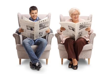 Giovane e una donna anziana che si siedono in poltrone e che leggono i giornali isolati su fondo bianco Archivio Fotografico - 93514755