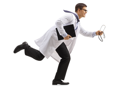 Full length profile shot of a doctor with a clipboard and a stethoscope running isolated on white background Standard-Bild
