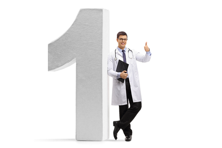Full length portrait of a doctor making a thumb up gesture and leaning against a number one figure isolated on white background