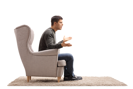 Young guy sitting in an armchair and arguing with someone isolated on white background