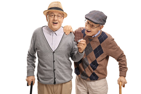 Elderly man sneaking up on another elderly man to grab a bite of his chocolate isolated on white background