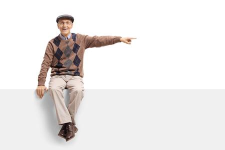 Senior assis sur un panneau et pointant isolé sur fond blanc Banque d'images - 94381618