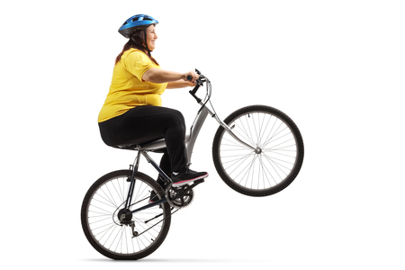 Overweight woman riding a bike and doing a wheelie isolated on white background