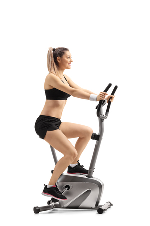 Full length profile shot of a young woman exercising on a cross trainer machine isolated on white background