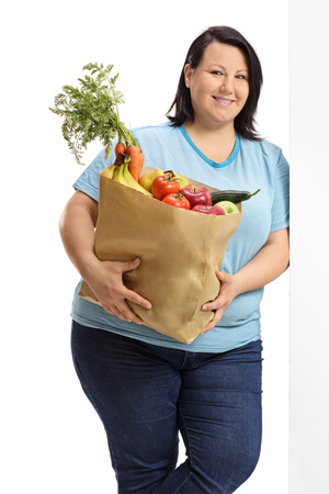 Overweight woman holding a paper bag filled with vegetables and fruit leaning against a wall isolated on white background