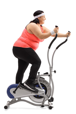 Full length profile shot of an overweight woman exercising on a cross-trainer machine isolated on white background