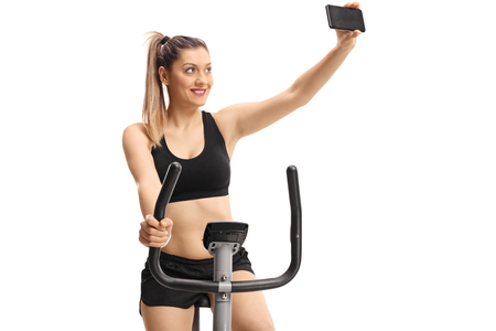 Young woman exercising on a cross-trainer machine and taking a selfie isolated on white background