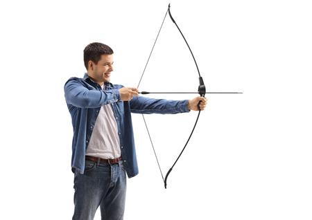 Jonge mens die met een boog en een pijl streeft die op witte achtergrond wordt geïsoleerd