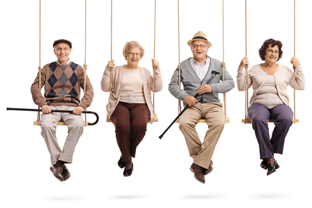 Cheerful seniors sitting on wooden swings and looking at the camera isolated on white background Reklamní fotografie