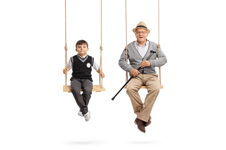 Little schoolboy and a mature man seated on swings isolated on white background Reklamní fotografie