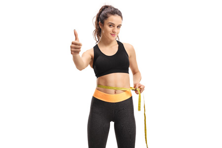 Young girl measuring her waist with a measuring tape and making a thumb up sign isolated on white background Banque d'images
