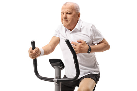 Mature man working out on an exercise bike and having a heart attack isolated on white background Stockfoto