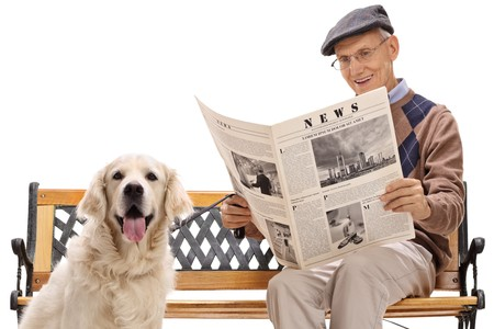 Senior with a labrador retriever dog sitting on a bench and reading a newspaper isolated on white background Banque d'images