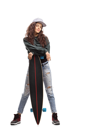 Full length portrait of a skater girl posing with a longboard isolated on white background Stock Photo