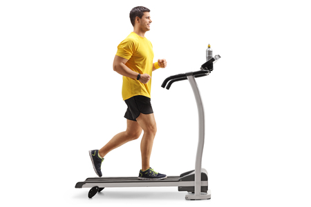 Full length profile shot of a young man running on a treadmill isolated on white background