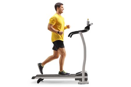 Longitud total foto de perfil de un joven corriendo en una cinta aislado sobre fondo blanco.