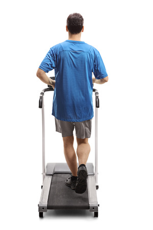 Full length rear view shot of a young man running on a treadmill isolated on white background