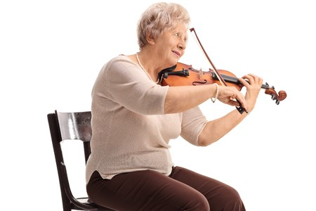 Elderly woman seated on a chair playing a violin isolated on white background 스톡 콘텐츠