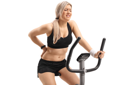 Young woman riding an exercise bike and experiencing back pain isolated on white background Stock Photo