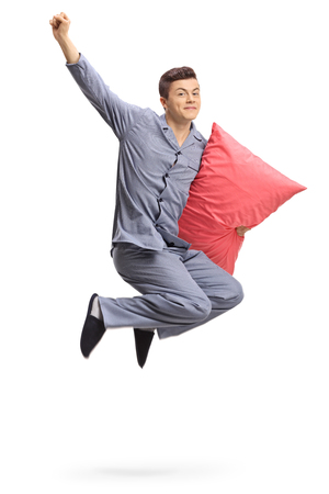 Teenager with a pillow jumping and gesturing happiness isolated on white background