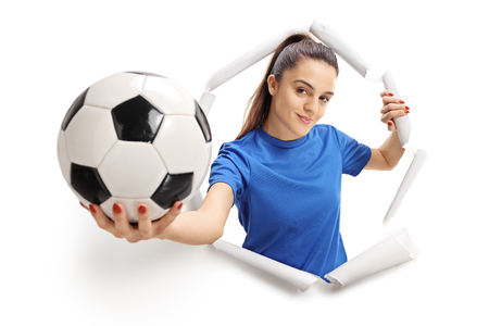 Female soccer player breaking through paper and showing a football