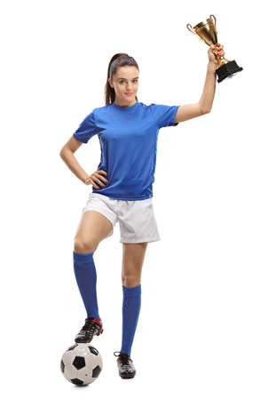 Full length portrait of a female soccer player with a football and a golden trophy isolated on white background Stockfoto