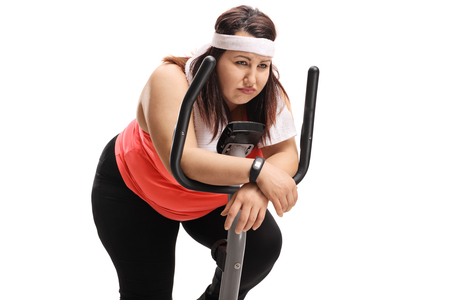 Tired overweight woman on an exercise bike isolated on white background