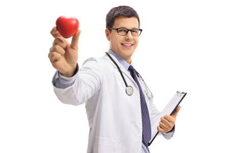 Doctor holding a clipboard and showing a heart isolated on white background Foto de archivo - 97848340
